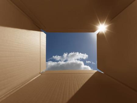 boite carton: Plan conceptuel illustrant la phrase �penser en dehors de la bo�te�. Implique pens�es inspirantes, de nouvelles id�es lumineuses, l'imagination et �chappant � la norme. La bo�te a des zones de l'espace de copie. Soigneusement plac�es pour montrer le ciel bleu clair et aussi lentille Banque d'images