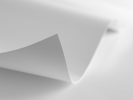curled corner: close up shot of curled corner on a plain piece of paper with a shallow depth of field Stock Photo