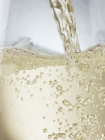 Close up of white wine or champagne being poured into a glass. Backlit to show clear, colored nature of the liquid. File has been comprehensively de dusted, some of the bubbles can look like sensor spots.