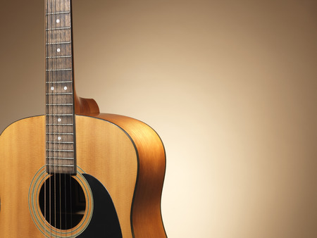 blues music: Shot of an acoustic guitar close up with a colored background and copy space. The graduated, halo effect in the background has been achieved naturally with lighting and was not the result of post production adjustments.