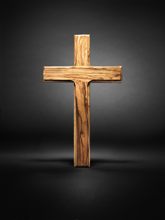 Shot of a wooden cross standing on a dark grey or black background with halo style graduated background