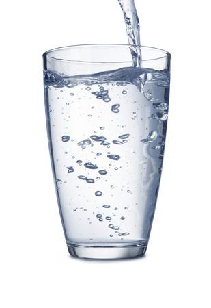 vaso con agua: Agua que vierte en el vidrio aislado en blanco Foto de archivo