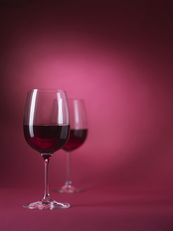 2 red wine glasses on red background