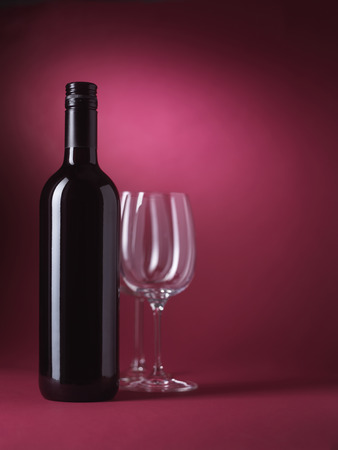 Red wine bottle and glasses on red background