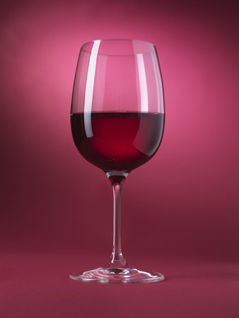 glass of red wine: Red wine glass isolated on red background Stock Photo
