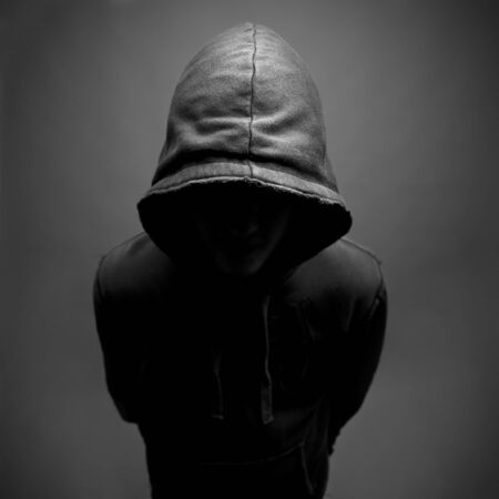 stereotypical: Dark and moody shot of youth wearing a hoody