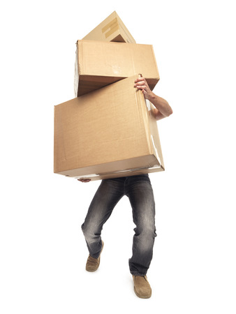 overburdened: shot of man struggling to carry boxes while moving house Stock Photo