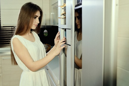 Cheerful smiling young white skin female with long brunette hair posing on the kitchen, set-up programing the refregerator, dressed in a light transparent white tunic. Morning makeup. Banque d'images
