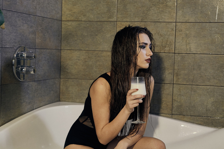 Girl in a black bathing suit holding a glass of milk in the bathroom. Conceptual fashion photography for design. Skin care and a healthy lifestyle. Closeup naked girl. Sexy woman portrait. Standard-Bild - 120312288