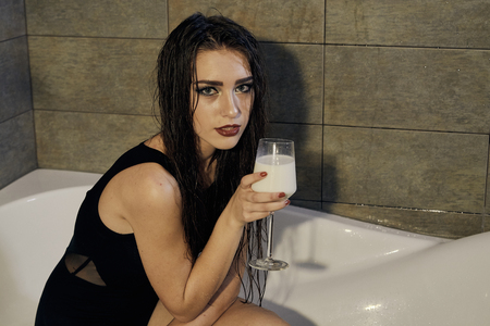 Girl in a black bathing suit holding a glass of milk in the bathroom. Conceptual fashion photography for design. Skin care and a healthy lifestyle. Closeup naked girl. Sexy woman portrait.