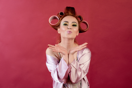 Young redhead woman with hair curlers dressed in peignoir, dressing gown posing on a burgundy background. Advertising concept with copyspace for design. Expression of different emotions. Pin-up style. Standard-Bild