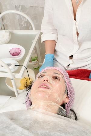 Mujer joven en salón de belleza haciendo peeling y procedimiento de limpieza facial. Dispositivo cosmético multifuncional. Procedimiento de ultrasonido. Atención sanitaria de equipos médicos. Masaje facial profesional.
