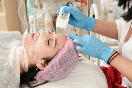 Young woman in beauty salon doing peeling and facial cleansing procedure. Cosmetic multifunctional device. Ultrasound procedure. Medical equipment healthcare. Face professional massage. Stock Photo