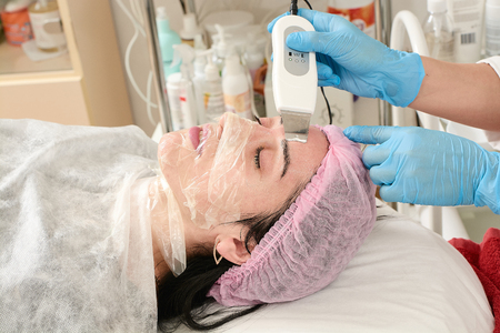Young woman in beauty salon doing ultrasound peeling and facial cleansing procedure. Cosmetic multifunctional device. Ultrasound procedure. Medical equipment healthcare. Face professional massage. Stock Photo