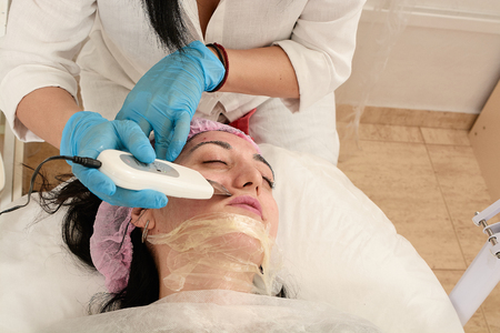 Young woman in beauty salon doing ultrasound peeling and facial cleansing procedure. Cosmetic multifunctional device. Ultrasound procedure. Medical equipment healthcare. Face professional massage. Banco de Imagens