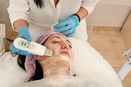 Young woman in beauty salon doing ultrasound peeling and facial cleansing procedure. Cosmetic multifunctional device. Ultrasound procedure. Medical equipment healthcare. Face professional massage. Foto de archivo