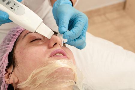 Mujer joven en salón de belleza haciendo peeling por ultrasonido y procedimiento de limpieza facial. Dispositivo cosmético multifuncional. Procedimiento de ultrasonido. Atención sanitaria de equipos médicos. Masaje facial profesional.