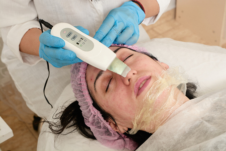 Young woman in beauty salon does ultrasound peeling and facial cleansing procedure. Cosmetic multifunctional device. Ultrasound procedure. Medical equipment healthcare. Face professional massage.