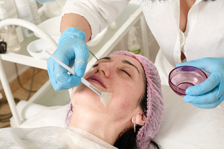 Young woman in beauty salon does skin moisturizing procedure after ultrasound peeling and facial cleansing procedure. Ultrasound procedure. Medical and beauty equipment healthcare. Banco de Imagens