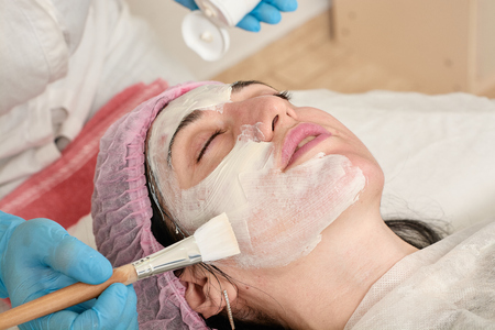 Young woman in beauty salon does make application of moisturizing, softening, regenerating mask before the rejuvenating, toning procedure darsonval on the face. Medical beauty equipment healthcare.