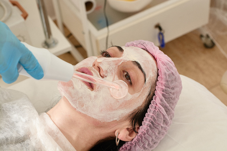 Young woman in beauty salon does rejuvenating, toning procedure darsonval on the face. Medical beauty equipment healthcare. Close-up beauty procedure. Modern darsonval's beauty procedure.