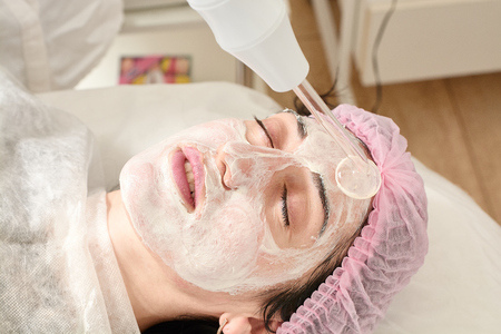 Young woman in beauty salon does rejuvenating, toning procedure darsonval on the face. Medical beauty equipment healthcare. Close-up beauty procedure. Modern darsonvals beauty procedure.