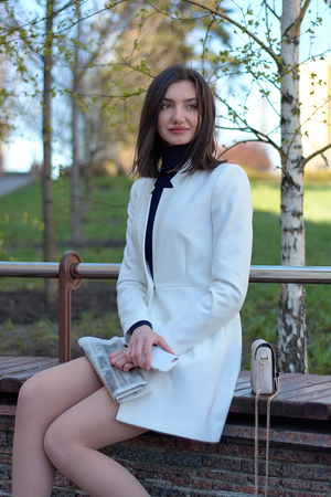 Elegant young woman dressed in a short white coat posing on a city street with a newspaper and mobile in her hands. Brunette woman. Modern urban woman portrait. Fashion business style clothes.