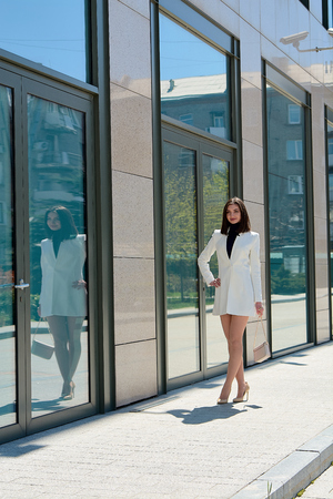 Elegant young woman dressed in a short white coat posing on a city street. Beautiful brunette woman. Modern urban woman portrait. Fashion business style clothes.