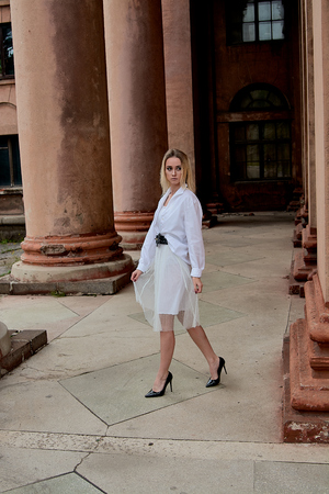Fashion look's woman. Young woman modern portrait. Young woman dressed in white skirt and shirt posing near the old looking soviet union's architectural building with large pillars and bas-reliefs. Imagens