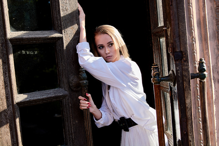 Young blonde woman in white skirt and shirt stands in the old wooden doorway. The old wooden door. Fashion woman. Young woman modern portrait.