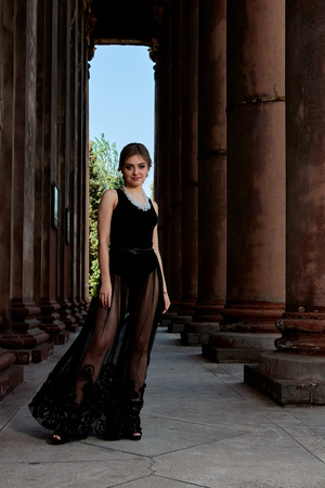 Young woman in transparent black dress near the ancient building. Vintage building. Fashion woman. Young woman modern portrait.