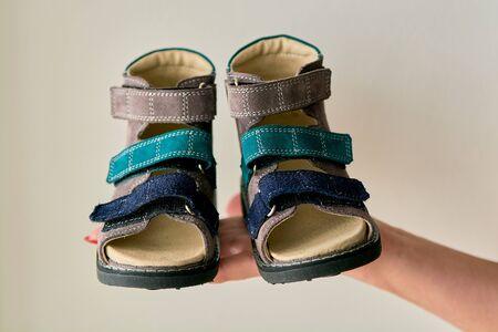 La mujer está sosteniendo un primer plano sandalias de zapatos ortopédicos especiales para niños hechos de cuero genuino. Zapatos cómodos aislados sobre fondo claro con copyspace. Imagen apta para publicidad. Foto de archivo