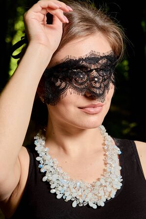 Young attractive woman in the sexy see-through, transparent, transpicuous, diaphanous, clear black dress and black lace masquerade venetian face mask posing outdoor at the green alley in the old park.