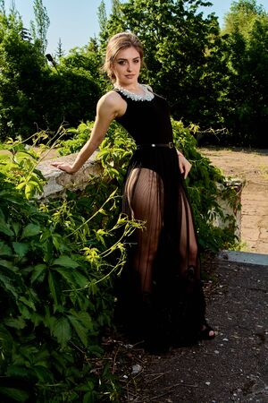 Young attractive woman in the see-through, transparent, transpicuous, diaphanous, clear black dress posing at summer sunny day outdoor in the old park. Fashion woman. Young woman modern portrait.