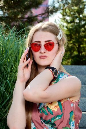 Young attractive woman. Red sunglasses, color dress, mobile phone, 5G, 4G, 3G, 2G, LTE network.