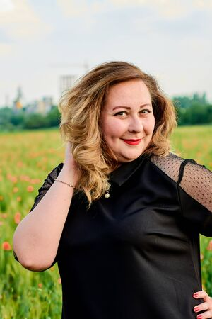 Long-haired plus sized woman in a black dress on a field of green wheat and wild poppies. Overweight fat woman. The concept of freedom and freshness. Summer vacation female symbol. Summertime flowers. Stok Fotoğraf