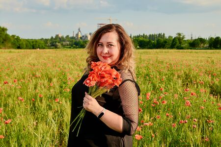 Long-haired plus sized woman in a black dress on a field of green wheat and wild poppies. Overweight fat woman. The concept of freedom and freshness. Summer vacation female symbol. Summertime flowers. Stockfoto