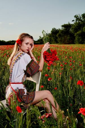 Long-haired blonde young woman in a white short dress on a field of green wheat and wild poppies.