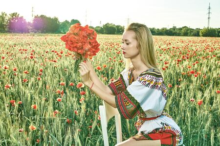 Long-haired blonde young woman in a white short dress on a field of green wheat and wild poppies. Slim sexy girl. A concept of freedom and freshness. Summer vacation female symbol. Summertime flowers.