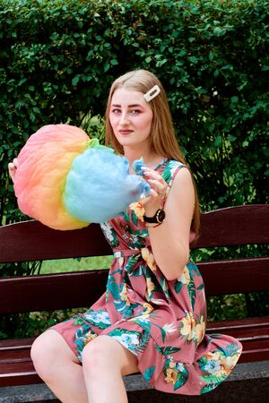 Happy joyful beautiful young woman with candy floss in the park at summer.