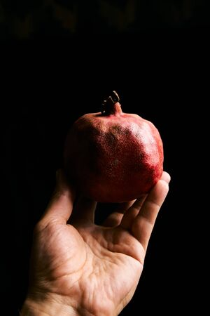 Fresh garnet in the man hand isolated on the black background with copyspase for cards and design for healthy life. Pomegranate. Stok Fotoğraf - 133946369