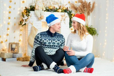 Beautiful young couple in love have fun on Christmas background. New Year background. Portrait of attractive just married couple. Modern family. Christmas stuff and decorations. Positive emotions.
