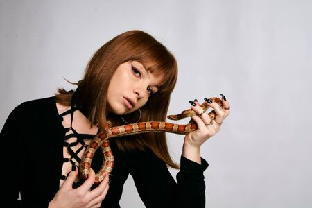 Beautiful woman in black bodywear and snake. Ginger model girl with fashion perfect make up. High end retouch. White background. Young woman with perfect fresh skin. Woman with snake around her.
