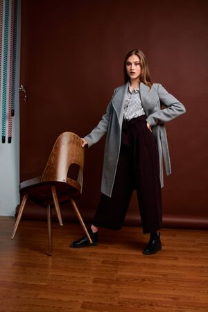 Independent young woman posing in the photostudio. Gorgeous young female in classic suit and grey coat. Brown background. Vintage chair style. Woman dressed in Man clothes. Fashionable clothes. Imagens