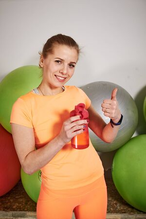 Slim athletic young woman in sportswear with water bottle in fitness club. Female workout. Fitness balls at the gym. Concept of good physical fitness and regular training in the gym. Water balance.