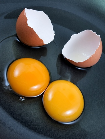 yolk: Eggs and shell cracked on black Teflon pan