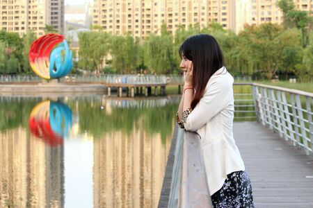 relying: Happy Chinese Girl Smiling in a Park, Next to the Lake