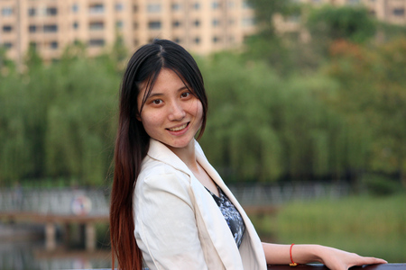 relying: Happy Chinese Girl Smiling in a Park