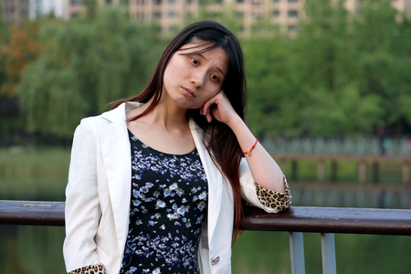 relying: Sad Chinese Girl Leaning on the Fence in Front of the Lake in a Park Stock Photo