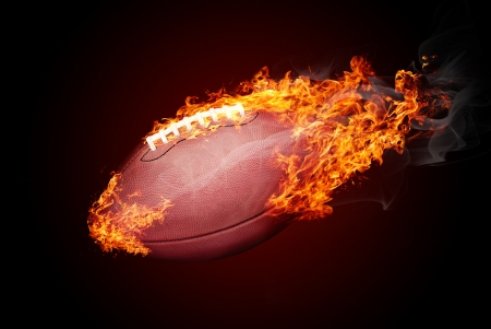 American football ball in fire isolated on dark red background - flying down photo